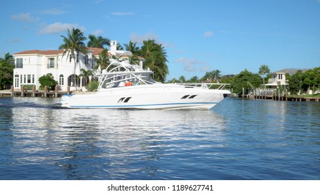 Large motor boat sailing through inner coastal waterway river during summer day time heading towards ocean for water activity. Expensive luxury in tropical destination