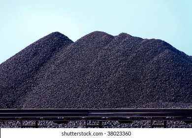 large mounds of coal with train tracks in the foreground