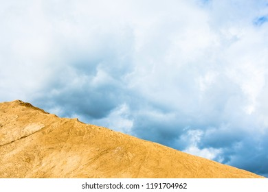 A large mountain of yellow sand, illuminated by the sun against the cloudy sky.
