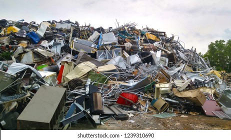 Large Multicolored Scrap Metal Pile with Appliances, Furniture, Twisted Metal Scraps on a Dirt Ground with a Green Tree in the Background and a Gray Overcast Sky