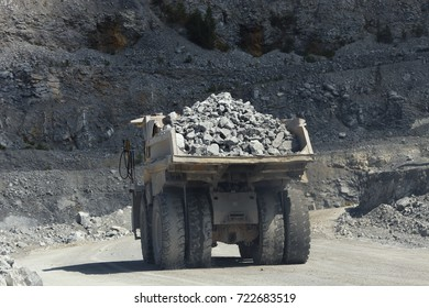 Large multi-ton truck carries stone ore in the quarry.
