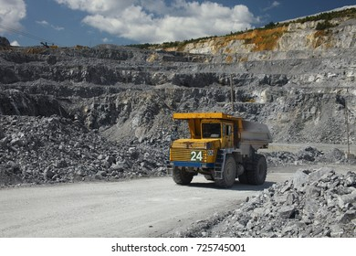 Large multi-toned mining truck in a limestone quarry on the background of blue sky with clouds. Quarry equipment. Mining industry.