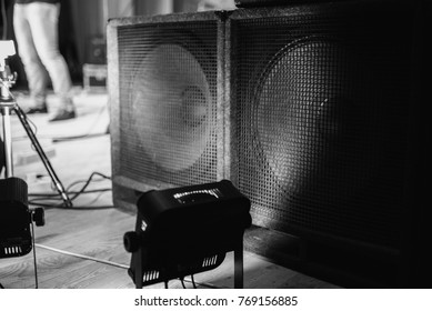 Large music speakers. Color lighting in the concert stage. Soffits illuminate the scene. Electric light. Equipment on stage for a concert