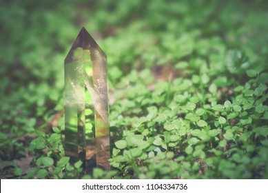Large mystical faceted quartz crystal on a grass nature background close-up