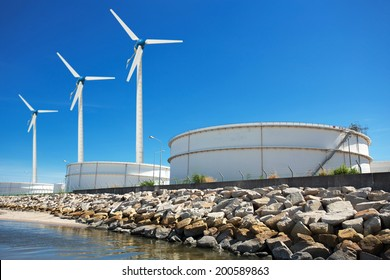 Large natural gas storage tanks with a windmill.