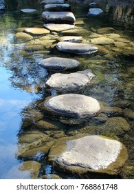 Large natural stepping stones in water with reflections of the sky and trees
