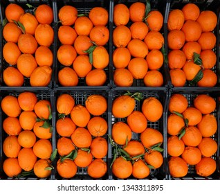 Large Navel oranges in black plastic boxes. Top view, food background