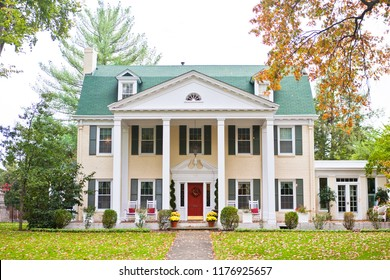 Large neoclassical style home with a turquoise roof, columns and a red door.