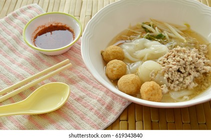 large noodles topping boiled minced pork and shrimp ball in soup with chili sauce