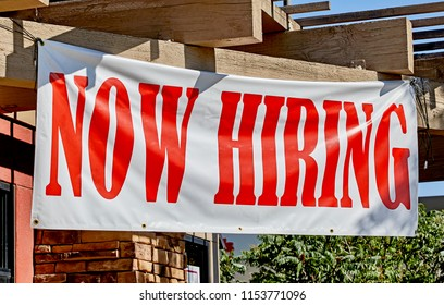 Large now hiring sign posted in the front of a business
