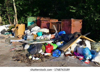 A large number of accumulated plastic bags and plastic packaging of household waste in garbage containers. The problem of garbage removal from the village, the concept of environmental pollution