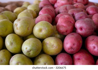 A large number of green and red potatoes stacked on a table beside each other