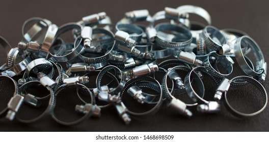 A large number of metal pipe clamps lies as if the hill on a dark background.