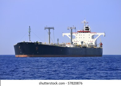 A large, ocean-going oil tanker ship at anchor.