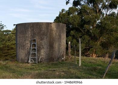 A large, old concrete water tank on a dairy farm in Ferndale, a rural area near Warragul in Gippsland, Victoria, Australia.