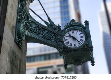 A large old decorated antique vintage clock in the city of Chicago with blurred background