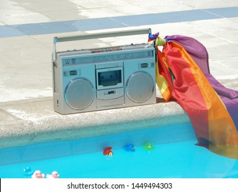 A large old radio at the edge of the pool with an LGTB flag and rubber ducklings floating in the water - Colorful Photo