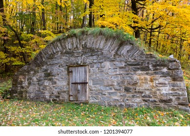 Large old stone root cellar with sturdy wooden door on Chemin Royal in the Fall, Beaupré Coast, Quebec, Canada