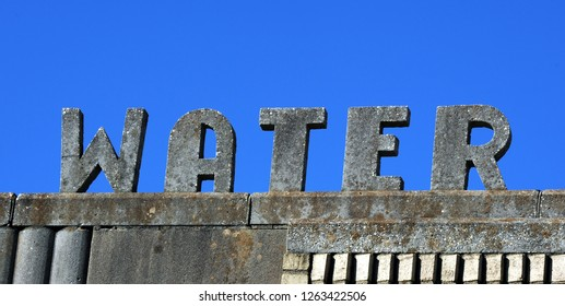 Large and old water sign would be welcome to someone stranded in the desert and desperate.  Vivid blue sky frames letters.