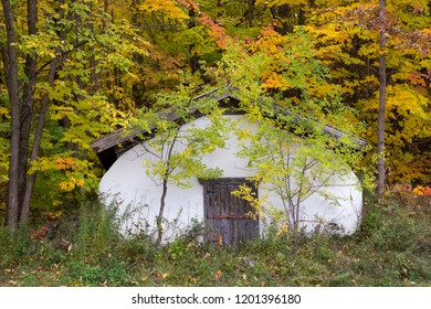 Large old wood and white stucco root cellar with sturdy wooden door on Chemin Royal in the Fall, Beaupré Coast, Quebec, Canada