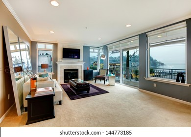 Large open bight living room with fireplace, TV and modern furniture.