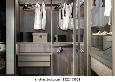 Large and open glass doors wardrobe with different stuff, shoes and male clothes in dressing room