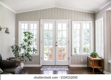 Large and open living room den sun room with windows on two sides and lots of natural light flowing in. Rear entrance back door to home - Shutterstock ID 1534152050