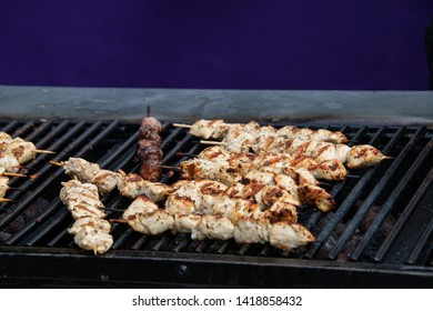 Large open outdoor barbecue grill cooking kabobs made of chunks of chicken on wooden skewers. The chicken is becoming nicely browned.