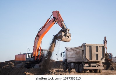 A large orange crawler excavator and a construction dump truck standing nearby while working on a sunny day against a blue sky. a large bucket pours earth into the back of a truck