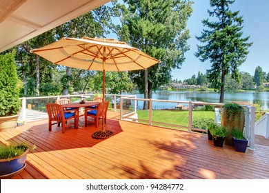 Large orange deck with umbrella and view of the lake