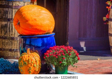 A large orange pumpkins sits on a tall blue planter with a smaller orage and green pumpking and red mums set at the base of the large ceramic blue planter.