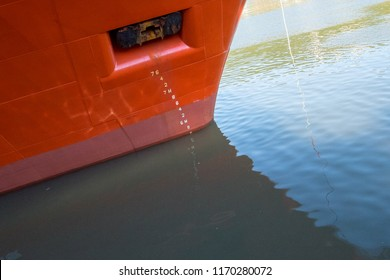 A large orange ship's bow with waterline numbers on the hull measuring the dept of the boat.