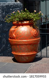 Large orange vase with tsfet on the sidewalk of the city.