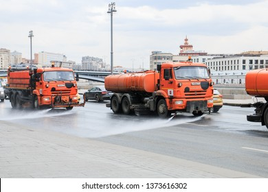 large orange watering machine washes part of the road with water in the city center, clean street. Russia, Moscow, April 2019.
