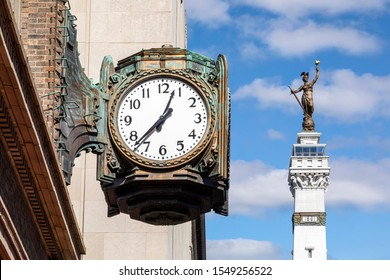 A large ornate bronze clock is backed by a monument topped with a statue in downtown Indianapolis, Indiana.