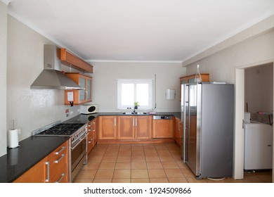 Large but outdated kitchen with wooden cabinets and granite counter top