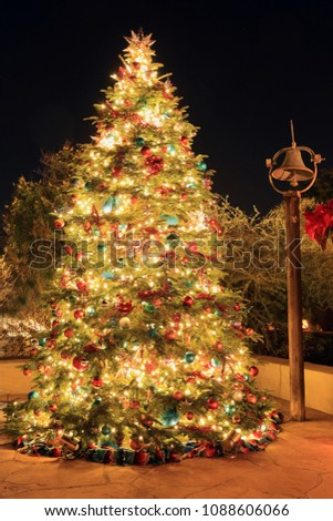 a large outdoor christmas tree with extensive lights and decorations at night