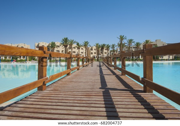 Large outdoor swimming pool with wooden bridge walkway at luxury tropical resort hotel in summer