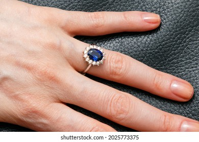 Large oval blue sapphire ring with diamonds on female hand