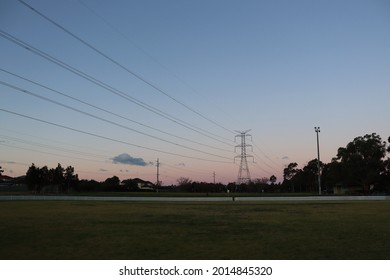 Large overland powerline tower against a purple, yellow and dark blue sky at sunset, next to a green grassed cricket over with white picket fence line.