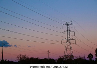 Large overland powerline tower against a purple, yellow and dark blue sky at sunset, next to a green grassed cricket oval.