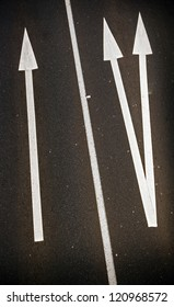 Large painted arrows on a freeway contrast with the bitumen for business concept