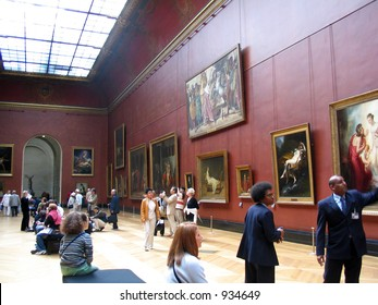 Large  painting gallery at the Louvre museum in Paris, people looking and museum guards.