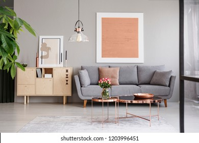 Large painting on a gray wall above an elegant sofa with cushions in a stylish living room interior with copper furniture