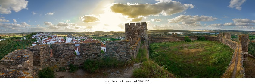 Large panorama of the empty castle walls of Terena overlooking the village of the same name under a blue clouded sky at the end of the day. Alentejo, Portugal.