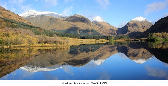Large panorama of snow capped summits of Buachaille Etive Mor and Beag reflected in Lochan Urr in Glen Etive in the Scottish Highlands.