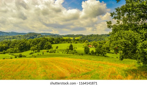 Large panorama of western Serbian village. Mountain region. Cottage on the top of the hill. Forest and fields in summer. Dramatic sky with clouds.
