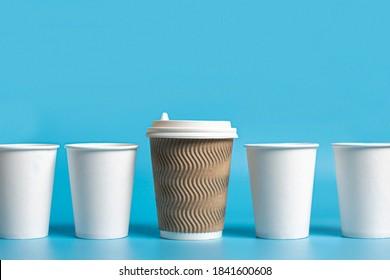 Large paper cup surrounded by white paper cups on a blue background. Concept boss, unique, friendly team, fimenism. Copy space
