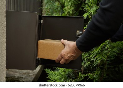 Large parcel in mailbox. Hand taking a large package in mailbox.