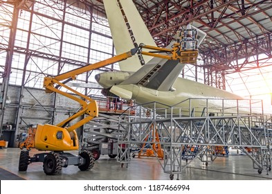 Large passenger aircraft on service in an aviation inside hangar rear view of the tail, on the auxiliary power unit
